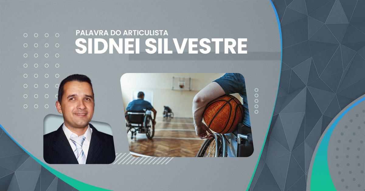 Na imagem, temos um cadeirante segurando uma bola de basquete em primeiro plano. Ao fundo, o restante do time na quadra.